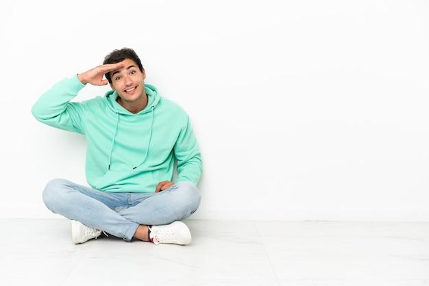 Un bell'uomo caucasico seduto sul pavimento che guarda lontano con la mano per guardare qualcosa