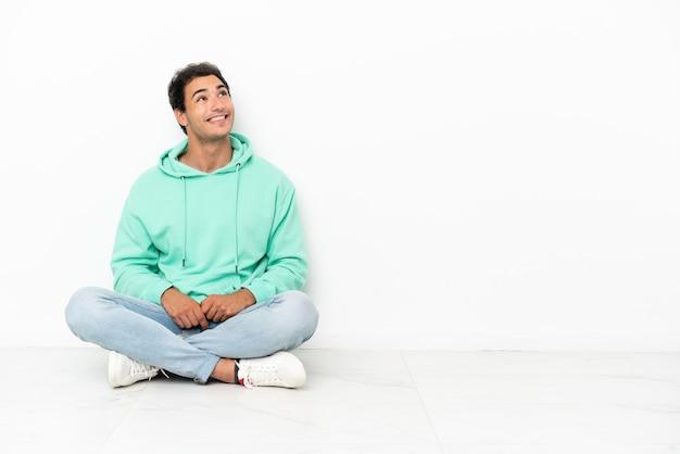 Bell'uomo caucasico seduto sul pavimento che guarda in alto sorridendo