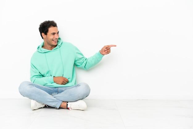 Bell'uomo caucasico seduto sul pavimento che punta il dito di lato e presenta un prodotto