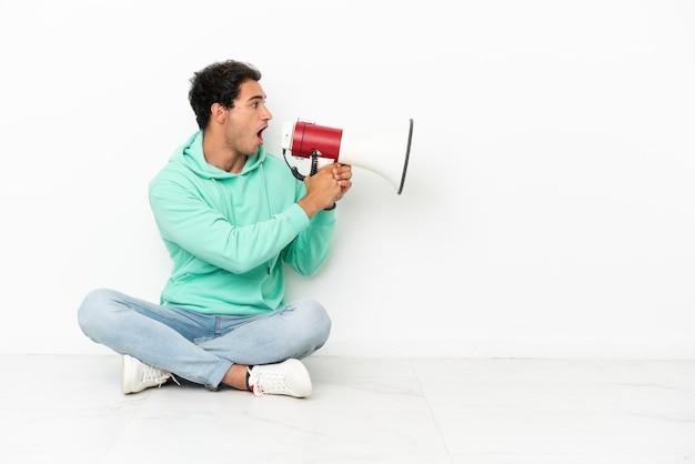 Bell'uomo caucasico seduto sul pavimento che grida attraverso un megafono