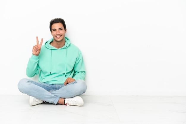 Caucasico bell'uomo seduto sul pavimento che sorride e mostra il segno della vittoria