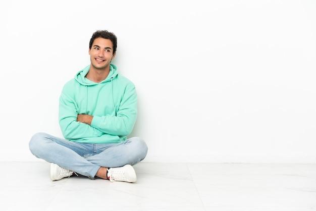 Bell'uomo caucasico seduto sul pavimento con le braccia incrociate e felice