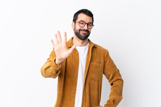 Caucasico bell'uomo con la barba che indossa una giacca di velluto a coste su bianco contando cinque con le dita