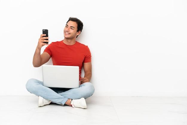 Bell'uomo caucasico con un laptop seduto sul pavimento che fa un selfie
