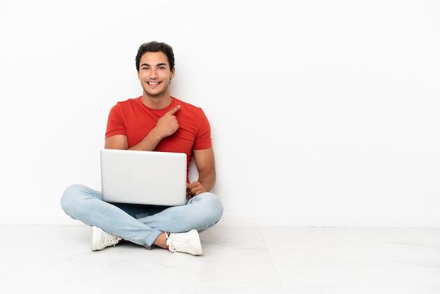 Bell'uomo caucasico con un laptop seduto sul pavimento che punta di lato per presentare un prodotto