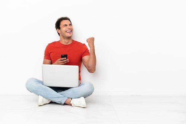 Bell'uomo caucasico con un laptop seduto sul pavimento con il telefono in posizione di vittoria