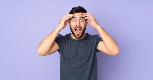 Uomo bello caucasico con l'espressione di sorpresa sopra la parete viola isolata