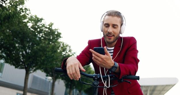 Giovane bello caucasico in cuffie che si appoggia sulla bici o sul motorino elettrico e sul canto. all'aperto. bello maschio elegante che ascolta la musica sullo smartphone in bicicletta. giocatore sul telefono cellulare.