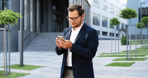 Giovane imprenditore elegante felice caucasico toccando o scorrendo sullo smartphone e in piedi in strada. messaggio di sms maschio bello sul telefono e sul sorridere. all'aperto.