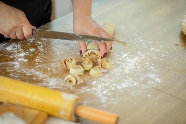 La casalinga caucasica in un grembiule taglia un rotolo di pasta con la cannella con un coltello.