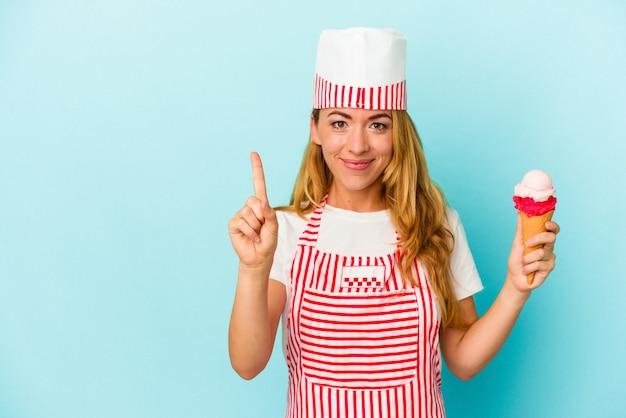 Caucasica gelatiera donna che tiene un gelato isolato su sfondo blu che mostra il numero uno con il dito.