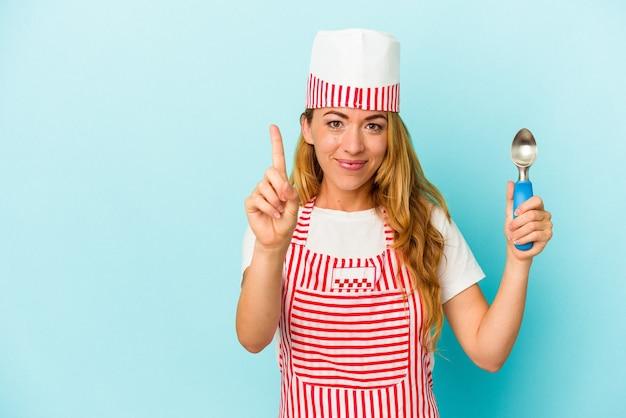 Donna caucasica del gelatiere che tiene una paletta del gelato isolata su fondo blu che mostra il numero uno con il dito.