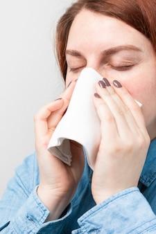 Caucasica malata donna sconvolta soffiarsi il naso in un tovagliolo su uno sfondo grigio isolato, ha avuto la febbre influenzale contratta l'influenza fredda