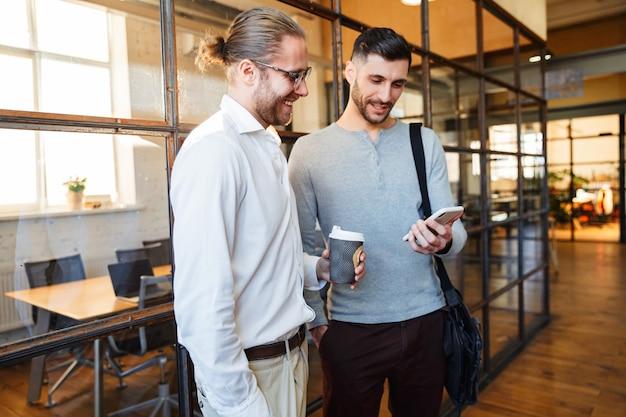 Colleghi gioiosi caucasici che parlano e usano il cellulare mentre si trovano in un ufficio moderno