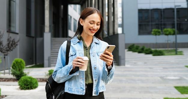 Giovane donna alla moda gioiosa caucasica toccando o scorrendo sullo smartphone e sorseggiando una bevanda calda al mattino in strada. bella felice messaggio di testo femminile sul telefono e bere caffè. al di fuori.