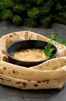 Zuppa khash caucasica in una ciotola, con torte lavash ed erbe aromatiche, primo piano. il piatto tradizionale armeno o turco è la zuppa, servita con verdure fresche, aglio e pane lavash croccante essiccato.