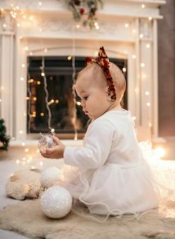 Una bambina caucasica in un soffice abito bianco e una fascia con le orecchie di tigre è seduta con la schiena in una stanza vicino al camino con i giocattoli dell'albero di natale