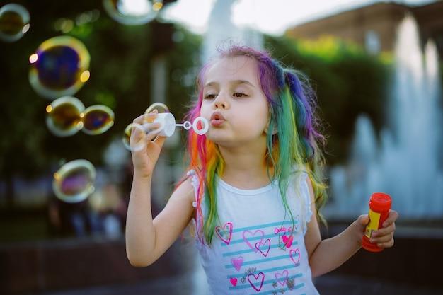 La bambina caucasica sta soffiando una bolle di sapone nel parco immagine con messa a fuoco selettiva