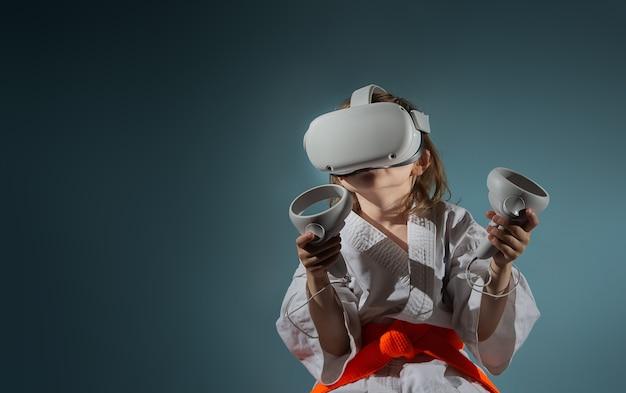 Bambina caucasica in uniforme di karate che gioca ai videogiochi con auricolare vr