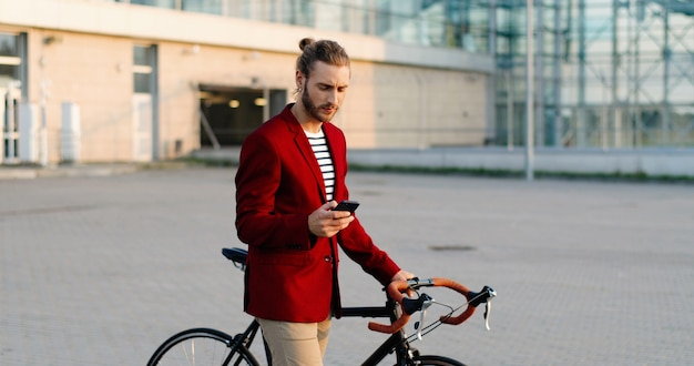 Ciclista maschio caucasico in stile casual e giacca rossa che porta la bici e toccando o scorrendo sullo smartphone in strada. bel giovane che cammina con la bicicletta e il messaggio di testo sul telefono cellulare.