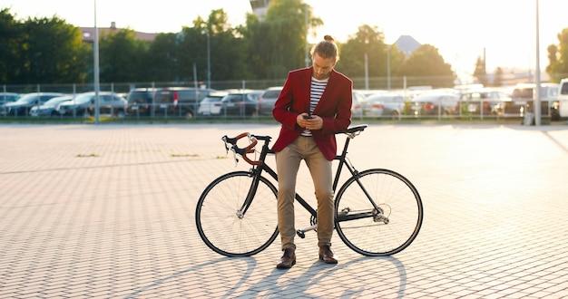 Ciclista maschio caucasico in stile casual e giacca rossa che si appoggia sulla bici e toccando o scorrendo sullo smartphone al parcheggio. bel giovane con la bicicletta e il messaggio di testo sul telefono. all'aperto.