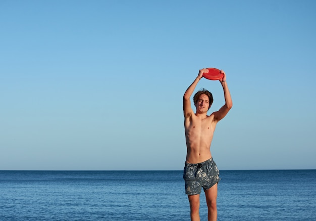 Un maschio caucasico che prende un frisbee in spiaggia durante il giorno