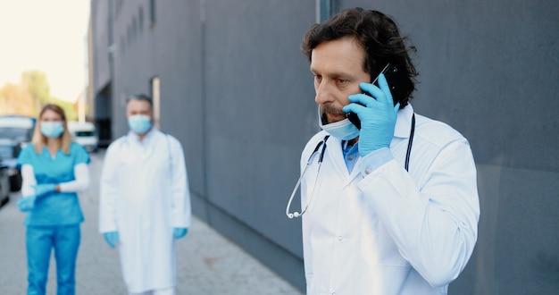 Medico maschio caucasico che parla sul telefono cellulare e inizia a correre e correre per aiutare il paziente. uomo medico fuori parlando sul cellulare e in esecuzione. squadra di medici sullo sfondo. chiamata d'emergenza. ambulanza.