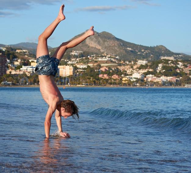 Un maschio caucasico che fa ginnastica in una spiaggia durante il giorno