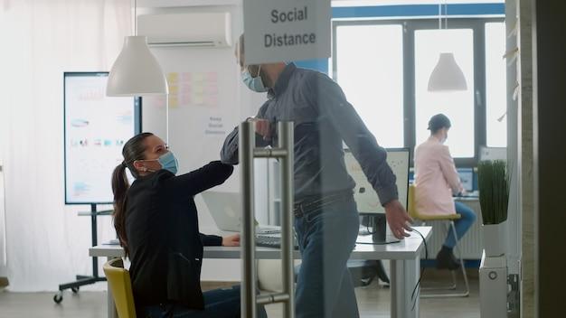 Maschio caucasico che saluta il suo collega con il gomito per evitare l'infezione da covid19. lavoratori che lavorano nel nuovo normale ufficio aziendale mantenendo le distanze sociali durante la pandemia globale di coronavirus