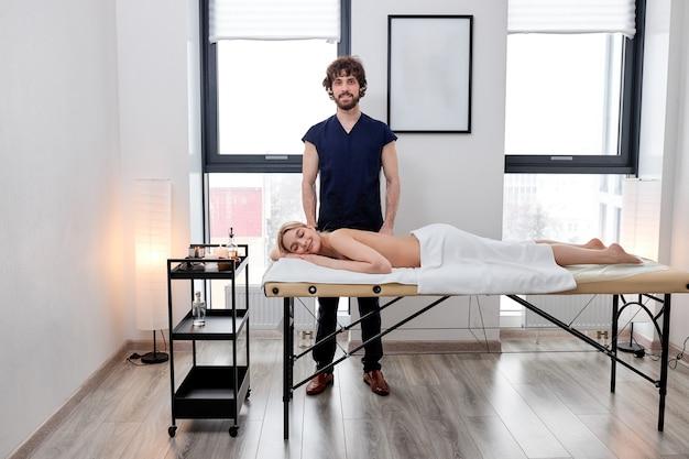 Il massaggiatore maschio caucasico si trova accanto alla cliente femminile rilassata sdraiata sul lettino da massaggio che riceve un massaggio da lui, massaggiatore barbuto in uniforme blu che posa alla macchina fotografica, nel salone della spa