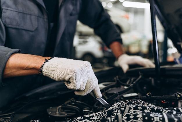 Il meccanico maschio caucasico ripara l'automobile in garage. manutenzione auto e concetto di garage di servizio auto. primo piano mano e chiave inglese