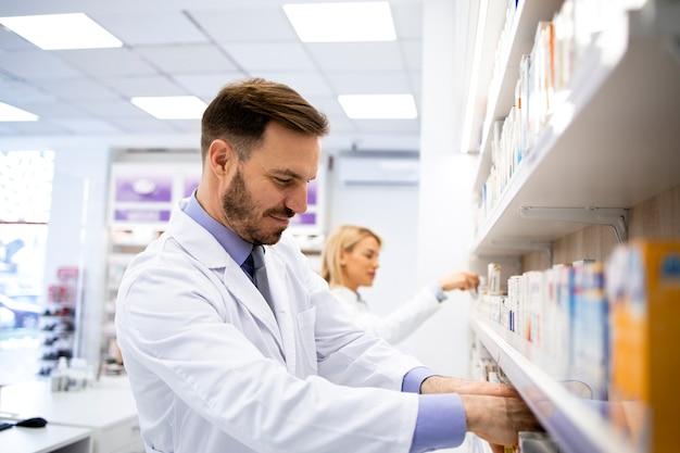 Farmacista maschio caucasico che lavora nella farmacia che organizza i farmaci.