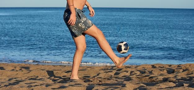 Un maschio caucasico che gioca a calcio su una spiaggia con un mare sullo sfondo