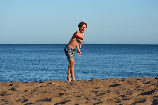 Un maschio caucasico che gioca a frisbee in un mare durante il giorno