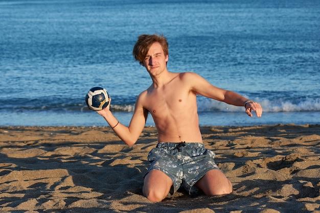 Un maschio caucasico che gioca con una palla su una spiaggia con un mare sullo sfondo
