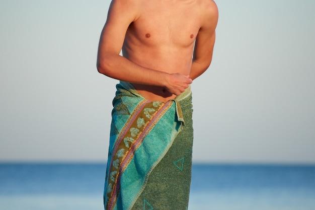 Il corpo di un maschio caucasico avvolto in un asciugamano verde con uno sfondo sfocato