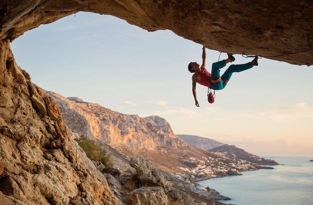 Uomo caucasico arrampicata percorso impegnativo che va lungo il soffitto in grotta al tramonto, contro la bella vista serale