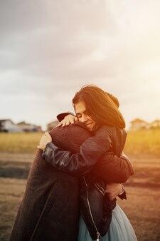 Uomo caucasico che abbraccia la sua ragazza con gli occhi chiusi alla luce del sole.
