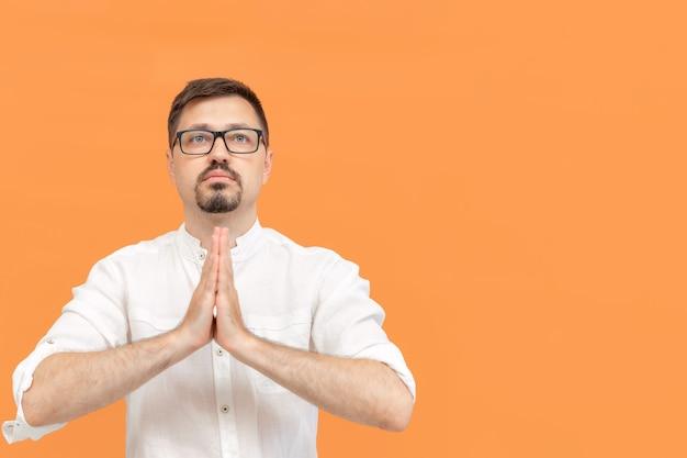 L'uomo caucasico incrociò le braccia in preghiera e chiese misericordia e compassione ritratto di uomo barbuto