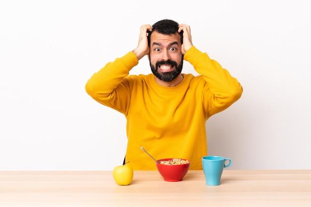 Uomo caucasico facendo colazione in un tavolo facendo gesto nervoso.