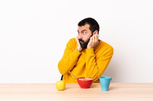 Uomo caucasico che fa colazione in un tavolo frustrato e che copre le orecchie.