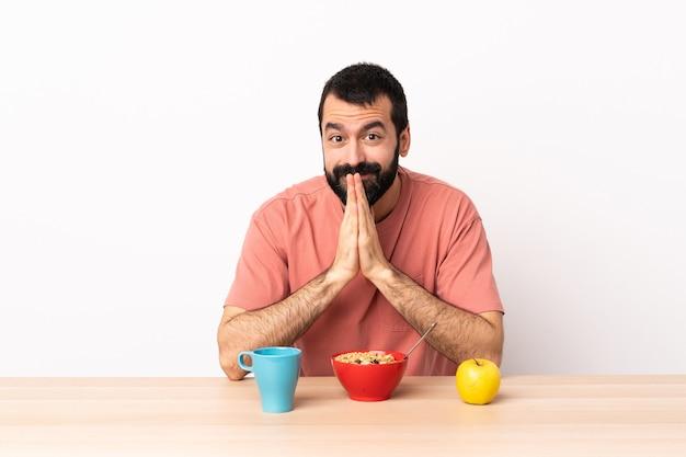 L'uomo caucasico facendo colazione in un tavolo tiene insieme la palma. la persona chiede qualcosa.