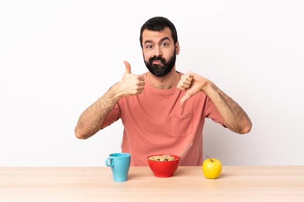 Uomo caucasico che mangia prima colazione in una tabella che fa segno buono-cattivo