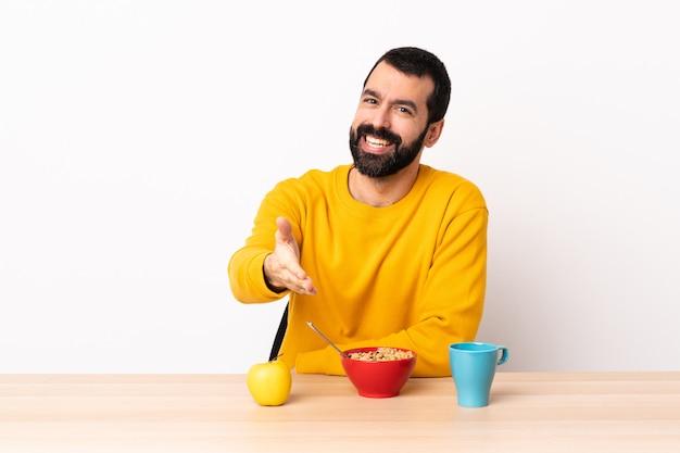 Uomo caucasico facendo colazione in un tavolo si stringono la mano per chiudere un buon affare