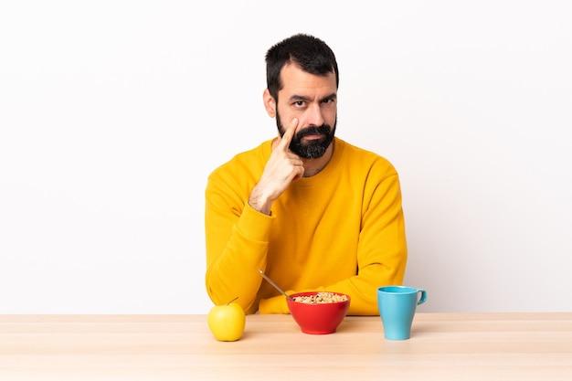 Uomo caucasico che fa colazione in un tavolo che mostra qualcosa.