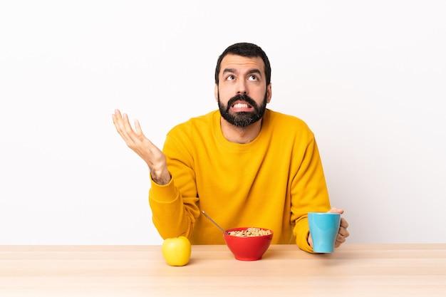 Uomo caucasico che mangia prima colazione in una tabella ha sottolineato sopraffatto.