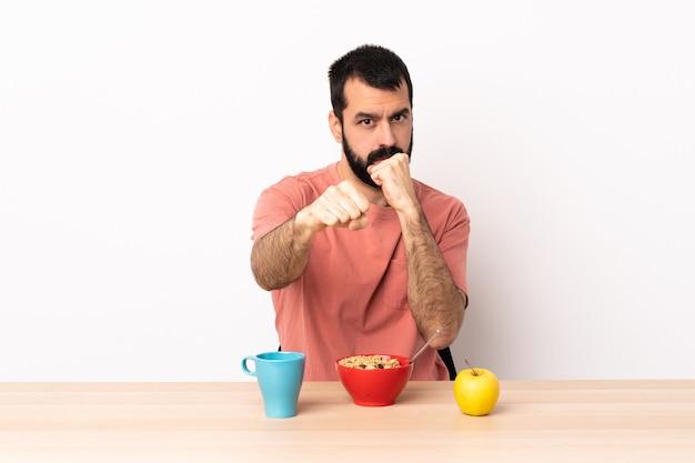 Uomo caucasico facendo colazione in un tavolo con gesto di combattimento.
