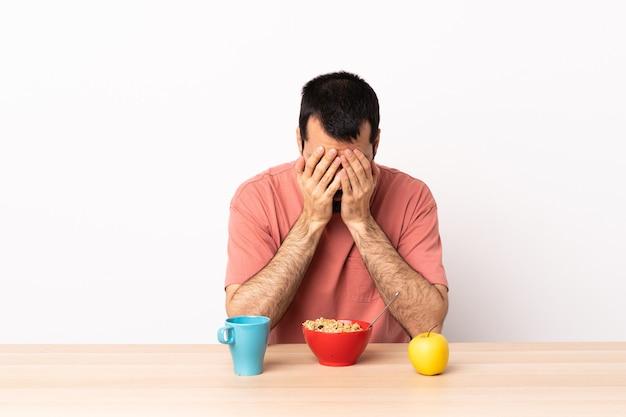 Uomo caucasico facendo colazione in un tavolo con espressione stanca e malata