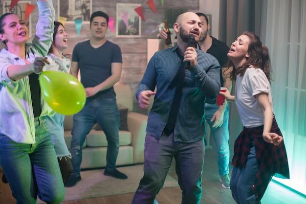 L'uomo caucasico e la sua ragazza fanno il karaoke alla festa dei loro amici.