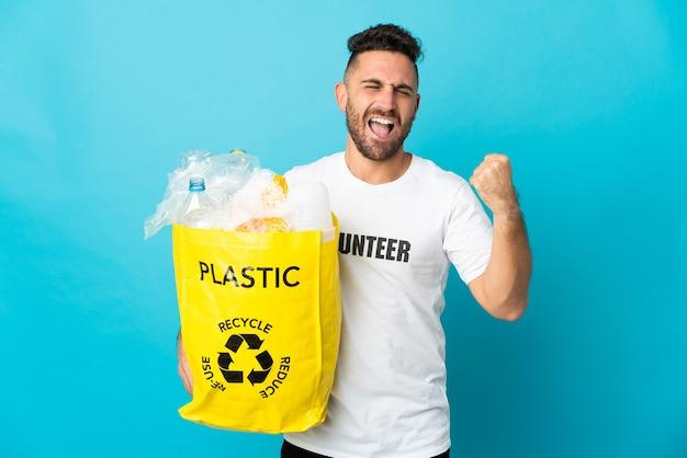 Uomo caucasico che tiene un sacchetto pieno di bottiglie di plastica da riciclare isolato sulla parete blu che celebra una vittoria